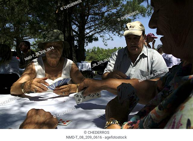 Two mature men and a mature woman playing cards, Provence, France