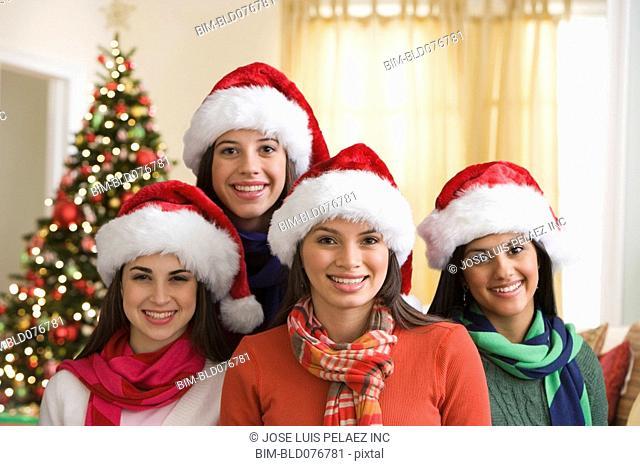 Teenage girls wearing Santa hats in front of Christmas tree