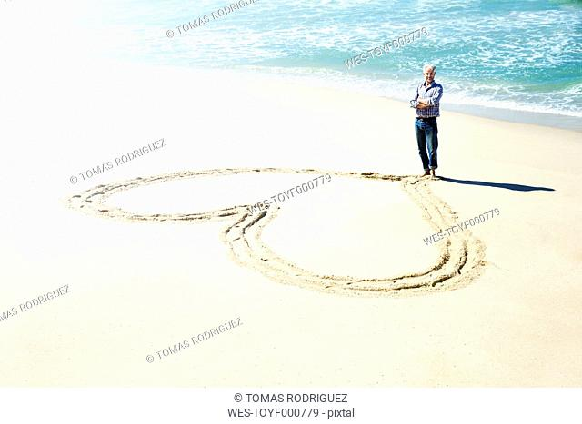 South Africa, man standing in front of heart carved in the sand of the beach