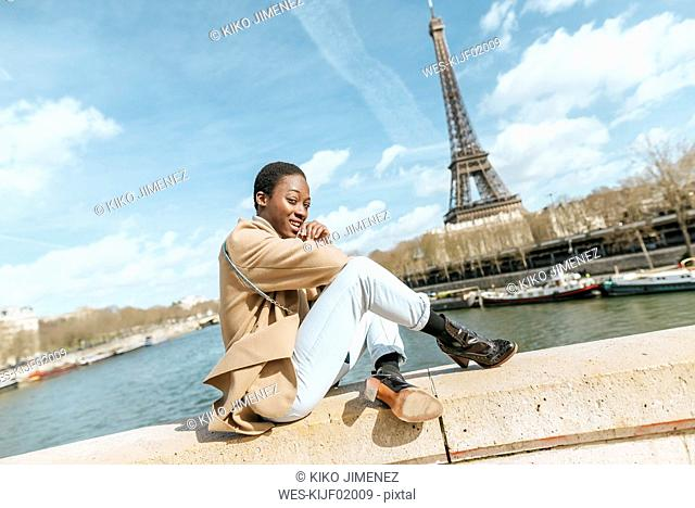 France, Paris, Woman sitting on bridge over the river Seine with the Eiffel tower in the background