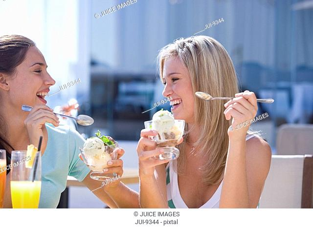 Two young women eating bowls of icecream outdoors, smiling at each other