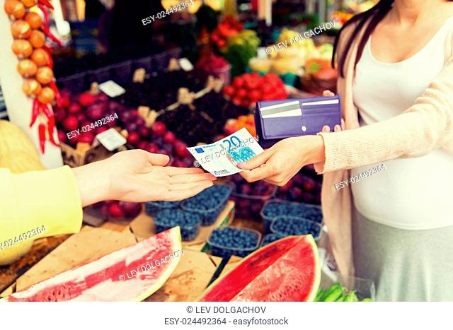 sale, shopping, pregnancy and people concept - close up of pregnant woman with wallet and money buying food at street market