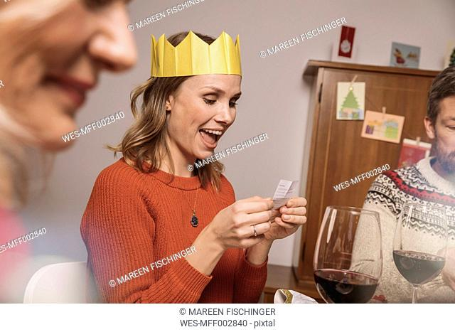 Woman with paper crown reading a poem from her Christmas cracker