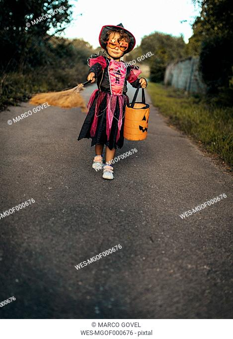 Little girl masquerade as a witch with halloween lantern and broom