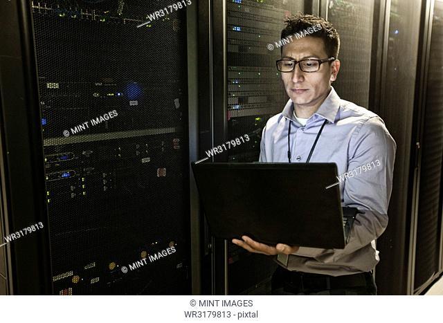 Hispanic man technician doing diagnostic tests on computer servers in a large server farm