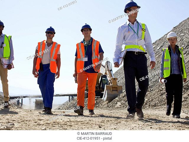 Workers and business people walking in quarry