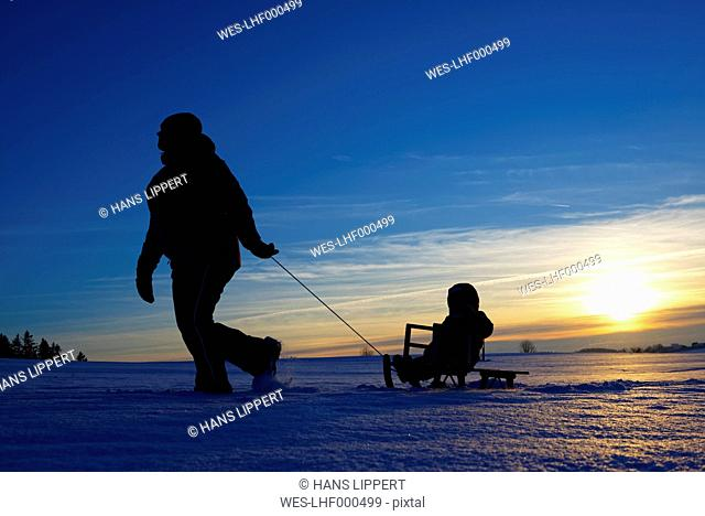 Mother and daughter sledging at sunset