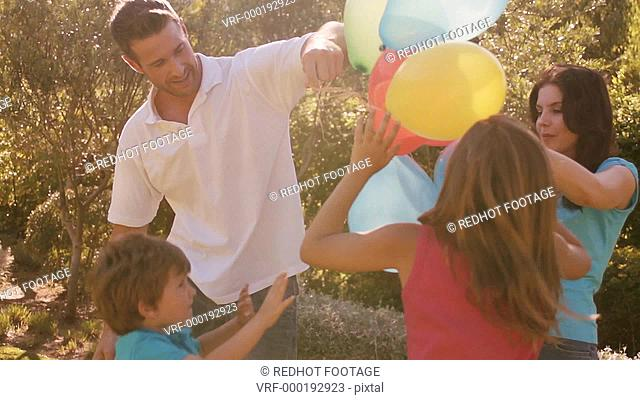 Family in park playing with balloons
