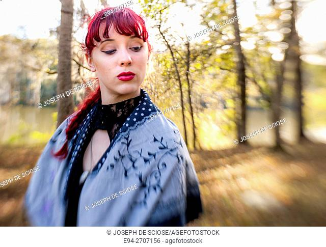 A pretty 23 year old red headed woman looking away from the camera, outdoors