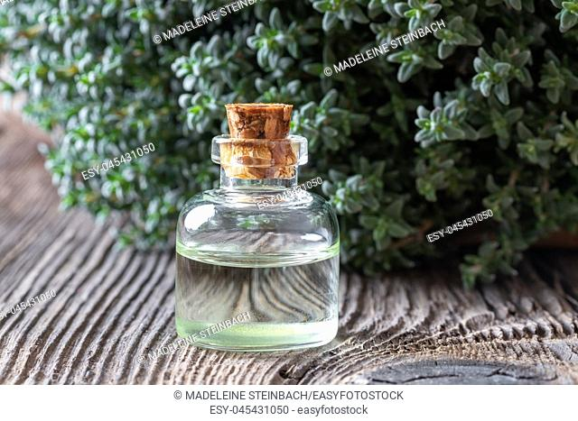 A bottle of essential oil with fresh thyme twigs in the background