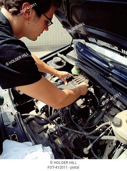 Young man checking a car battery