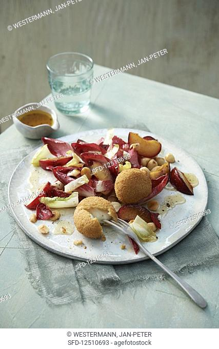 Red and yellow chicory salad with baked mozzarella, red plums and nut dressing