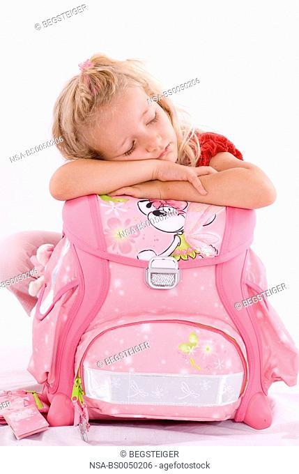 school girl sleeping on school bag