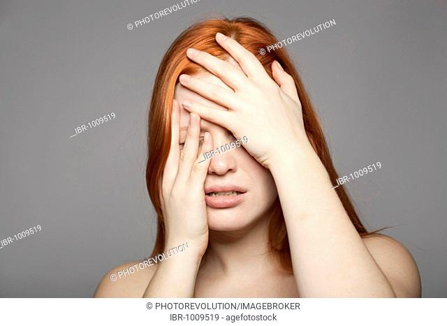 Young, red-haired woman, distressed, sad