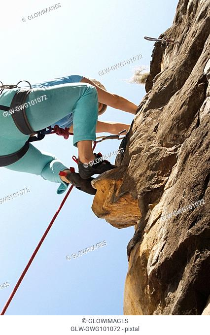 Low angle view of a female rock climber scaling a rock face