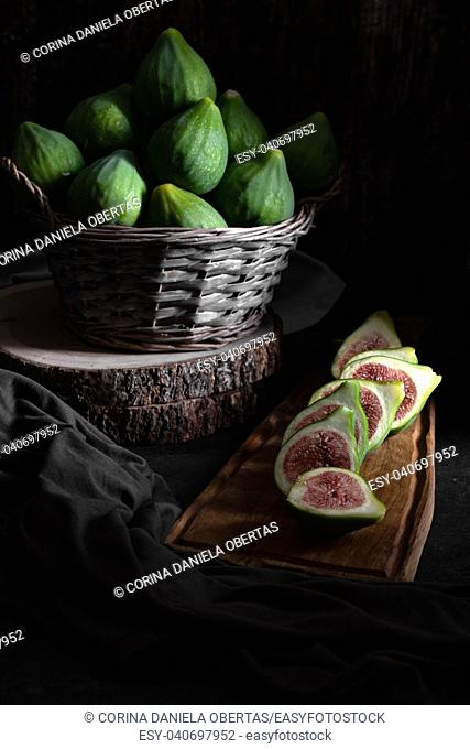 Still life with figs inside a basket on an old wooden table