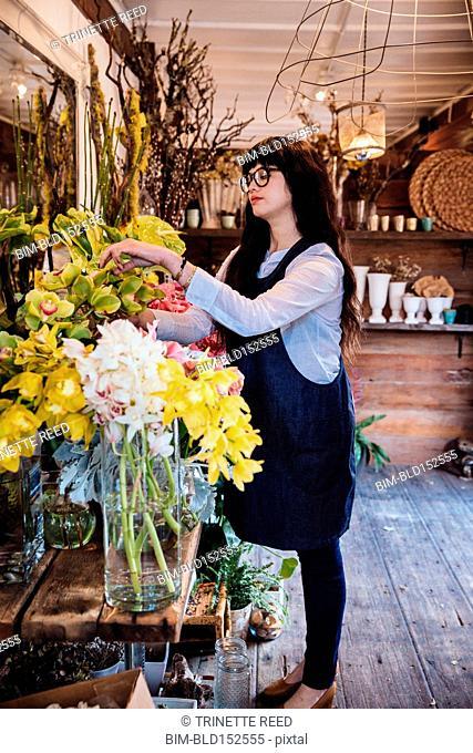 Mixed race florist arranging flowers in shop