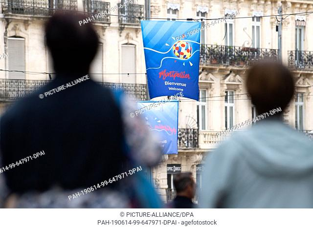 14 June 2019, France (France), Montpellier: Football, women: WM, Montpellier : Passers-by walk under the flags of the world championship on which...