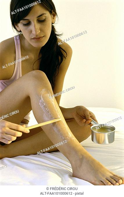 Young woman removing body hair with hot wax