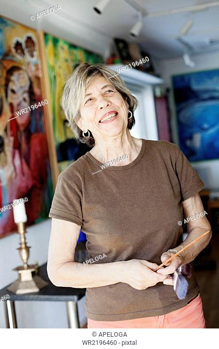 Smiling senior female artist holding paint brushes in studio