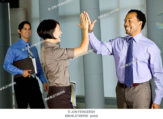 Multi-ethnic co-workers high fiving in office