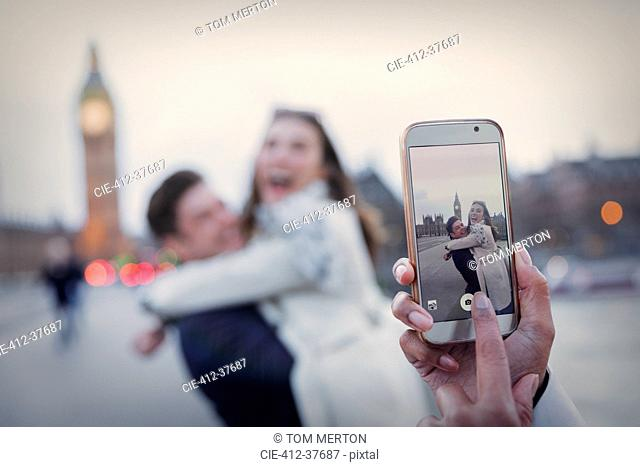 Personal perspective, playful couple hugging and being photographed with camera phone near Big Ben, London, UK