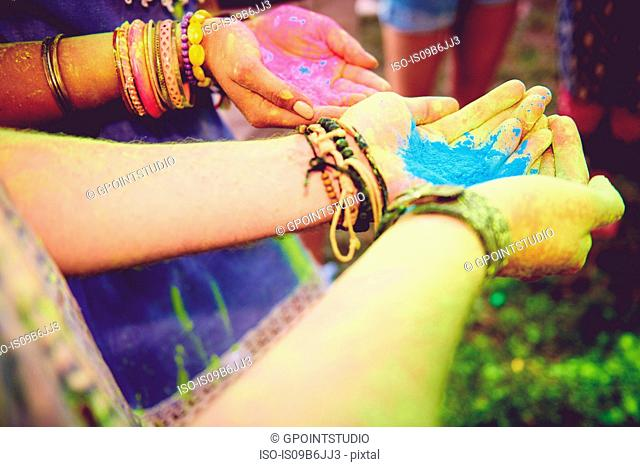 Pink and blue chalk cupped in young couples hands at festival
