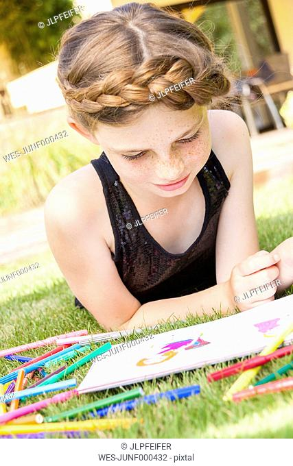 Girl lying on a meadow with colouring book and felt tip pens