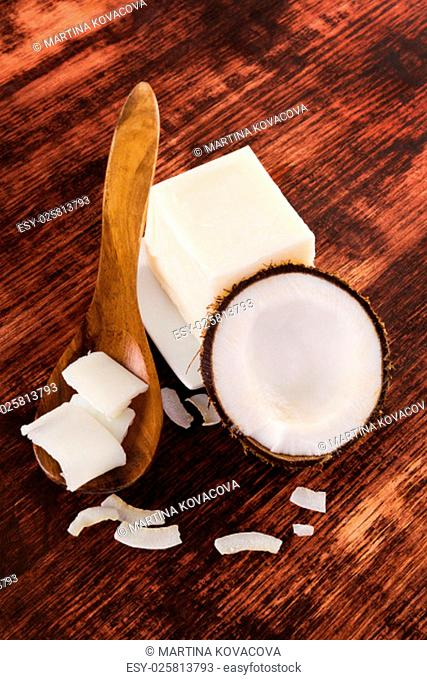 Coconut oil background. Hard coconut oil, coconut flakes and coconut on brown wooden background. Healthy ecological living