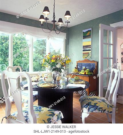 DINING ROOM - White Queen Anne chairs. Shiny black pedestal table, Roman shades, green walls with textured effects, white trim, floral arrangement