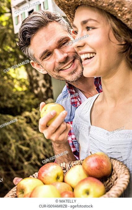 Couple outdoors, holding apples