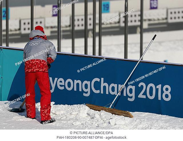 A helper shoveling snow at the shooting range during biathlon training in the Alpensia Biathlon Centre in Pyeongchang, South Korea, 08 February 2018