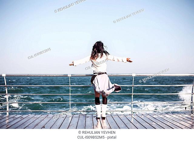 Mid adult woman looking out from pier with arms open, rear view, Odessa, Odeska Oblast, Ukraine