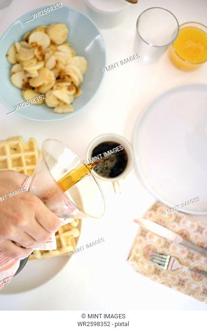 High angle view of a breakfast table, waffles, fried potatoes, coffee and juice