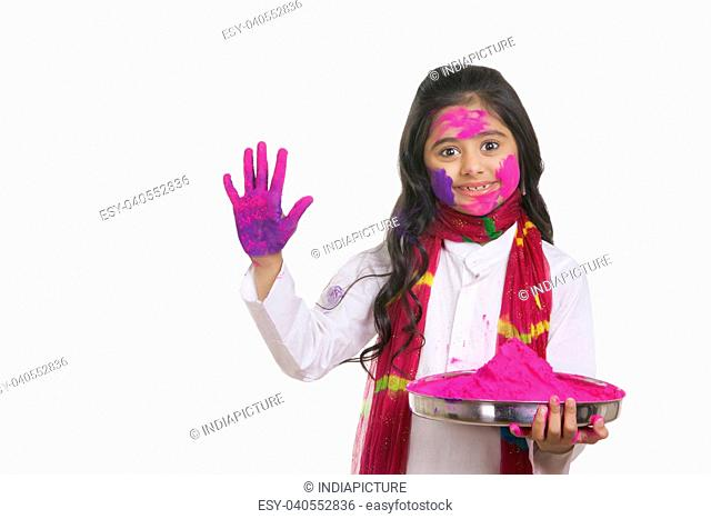 Portrait of a girl with a thali of holi colour