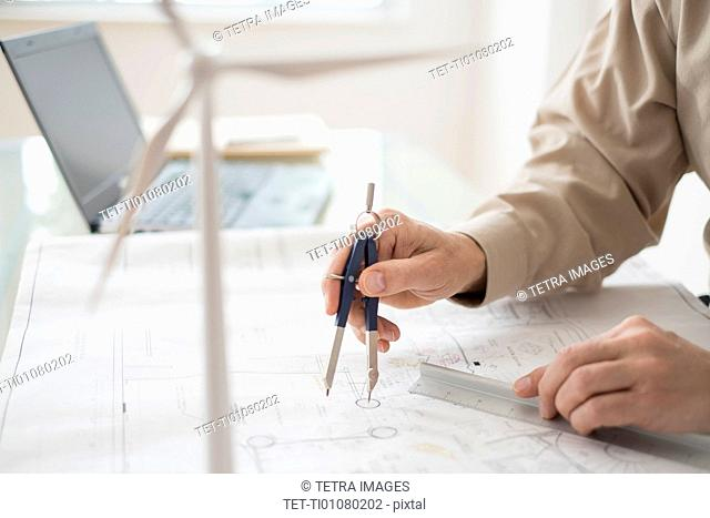Close up of man's hands using compass while drawing plans