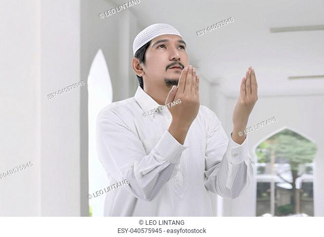 Religious asian muslim man with white cap praying on the mosque