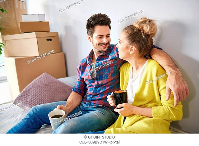 Young couple at home, surrounded by cardboard boxes, drinking coffee, smiling