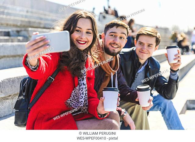 Russia, Moscow, group of friends taking a selfie and showing their cups of coffee