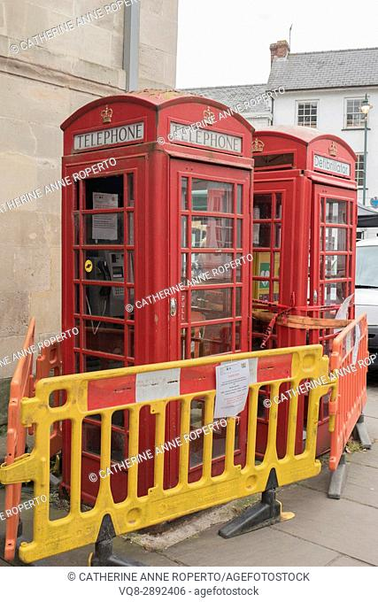 Red telephone boxes and defibrillator cordoned off with yellow and orange barriers in Monmouth market square, Wales, UK