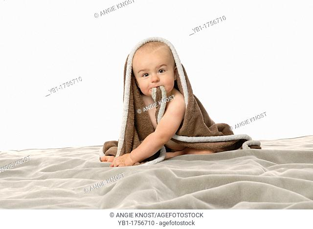 Cute one year old baby boy is sitting up with a blanket wrapped around him  He is biting the blanket and making a funny face