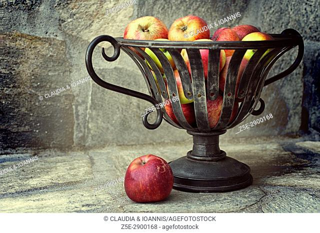 Still life with red apples in a metal basket on a stone bench