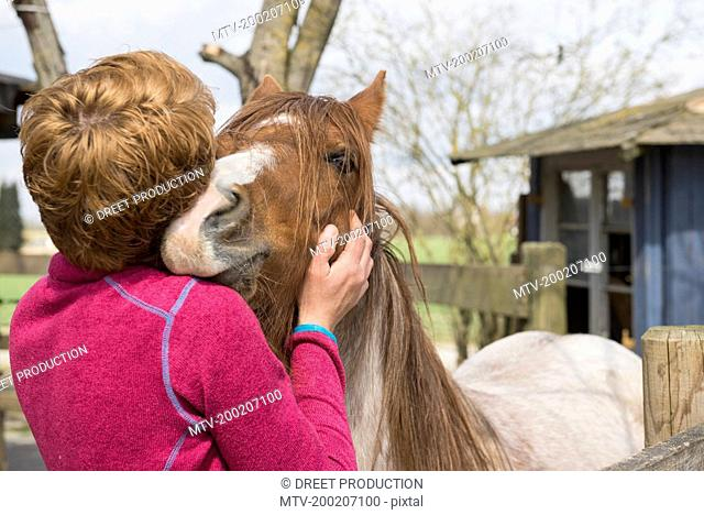 Woman hugging horse in stable, Bavaria, Germany