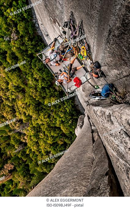 Rock climbers lying on portaledge, Muir Wall, on el Capitan, Yosemite Valley, California, United States