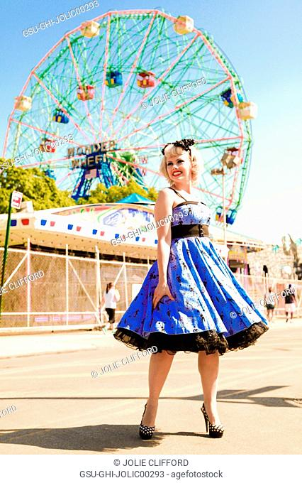 Smiling Young Adult Woman Twirling in Dress in Front of Ferris Wheel