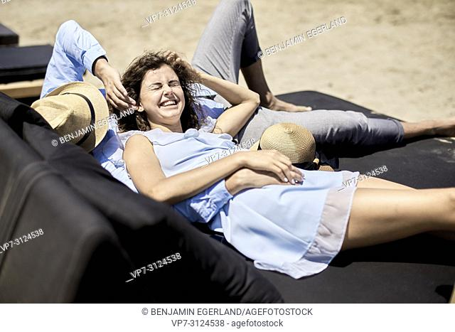 couple lying on sunbeds, love, vacations, summer, happiness, togetherness