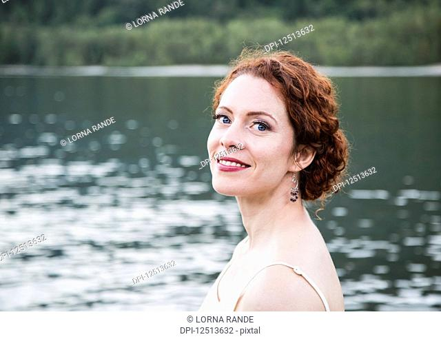 Portrait of a woman with red hair and a lake in the background; British Columbia, Canada
