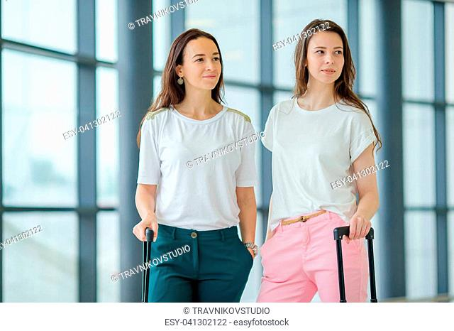 Young women in international airport walking with her luggage