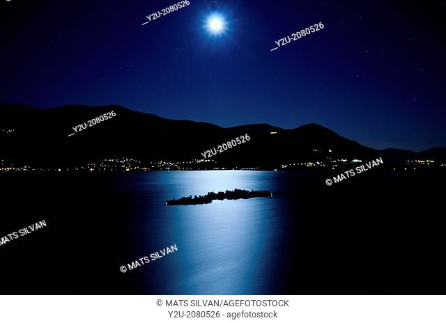Moon light reflected over an alpine lake maggiore with brissago islands and mountains at night in ticino switzerland