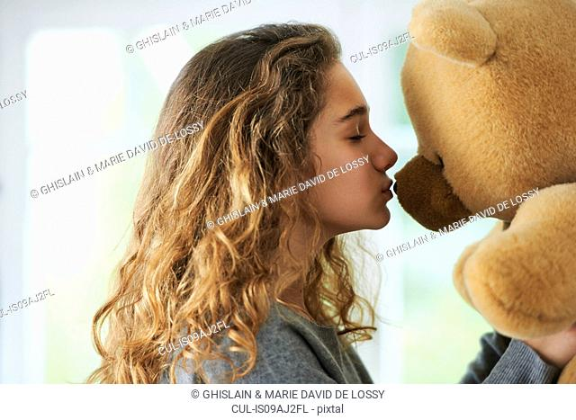 Portrait of young girl kissing teddy bear
